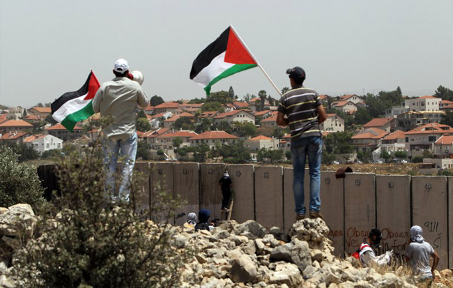 NILIN : Palestinian protesters wave the national flag as their comrades climb Israel's controversial separation barrier during clashes with Israeli security forces following a demonstration against Israeli settlements and its separation wall, in the West Bank village of Nilin near the Jewish settlement of Hashmonaim (background), on May 31, 2013. AFP PHOTO/ ABBAS MOMANI