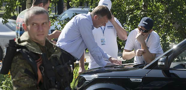 Alexander Hug, deputy head of the OSCE mission to Ukraine, center, and his colleagues discuss the situation around the MH17 crash site. - AP Photo/Dmitry Lovetsky