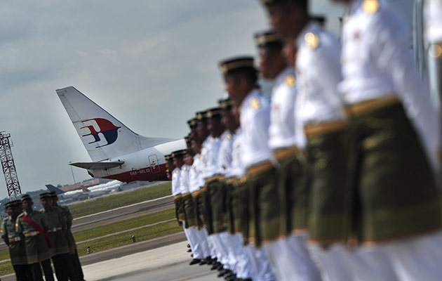A Malaysia Airlines plane passes by as Malaysian army personnel conduct the final rehearsal for the National Day of Mourning at the Bunga Raya Complex at KLIA. - Astro AWANI/Shahir Omar