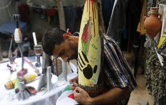 Palestinian artist Mohammed al-Zamar works on an adorned used and diffused ammunition round on September 24, 2014, in the Bureij refugee camp in central Gaza - AFP PHOTO/MOHAMMED ABED