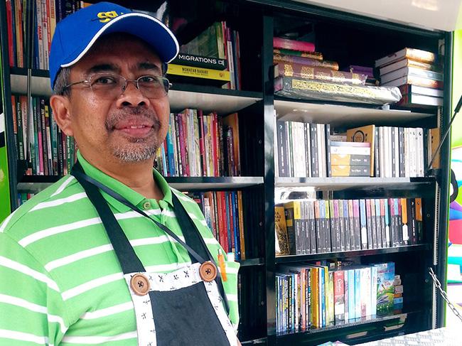 Muhamad Ali berdiri di hadapan kedai buku bergeraknya. -- Foto Bernama