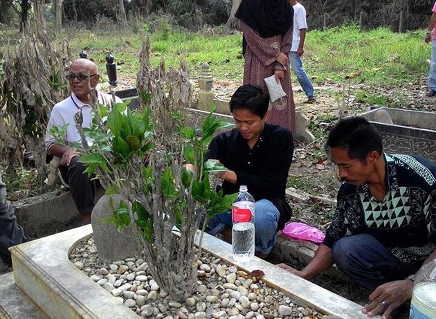 Atai anak saudara Allahyarham bersama keluarga dan peminat di pusara Allahyarham Sudirman Hj Arshad di Tanah Perkuburan Chengal, Pahang. - Foto Facebook Sudirman Hj Arshad
