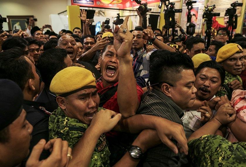 Kejadian tolak-menolak dan rempuhan antara satu sama lain berlaku semasa Muhyiddin beredar dari Dewan Tun Dr Ismail. - Foto Astro AWANI / SHAHIR OMAR