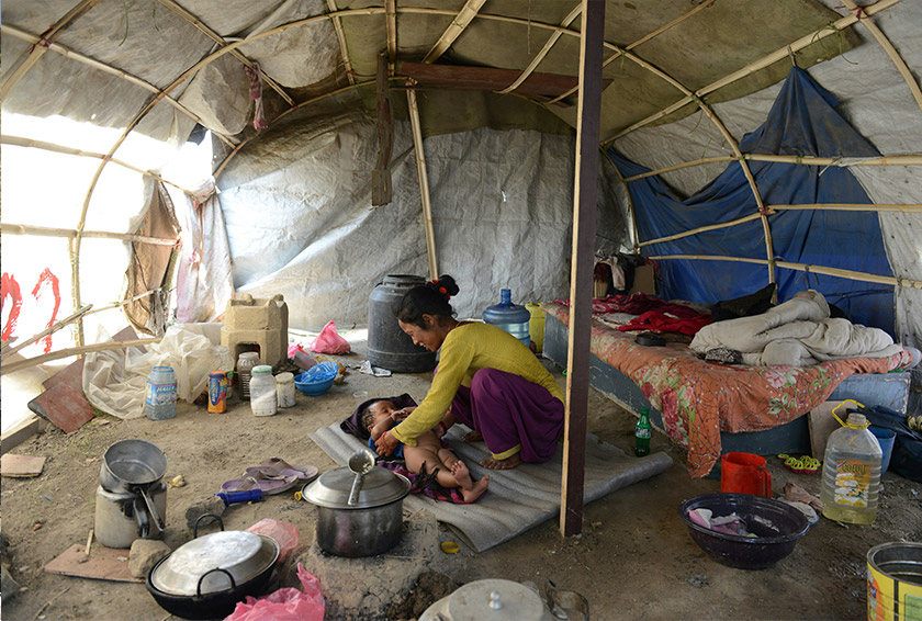 Menuka Rokaya caring for her child in the tent she lives with her husband and the nine-month-old in Ramechhap on the outskirts of Kathmandu on April 21, 2016. - AFP Photo