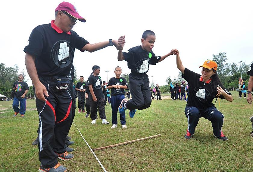 Pelajar cacat penglihatan dari Sekolah Kebangsaan Pendidikan Khas Kuala Terengganu Adid Muayyad Zamri, 12, dibantu oleh gurunya untuk melompat sewaktu menyertai acara Forward Squat Jump sempena Hari Sukan Negara di Batu Burok hari ini. - Foto Bernama