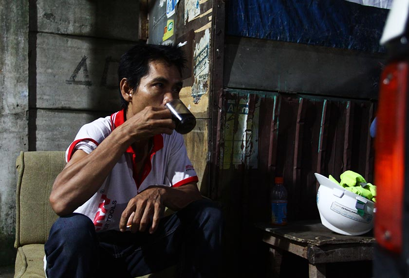Pak Tukin takes a break from work with a cup of coffee. - Karim Raslan Photo