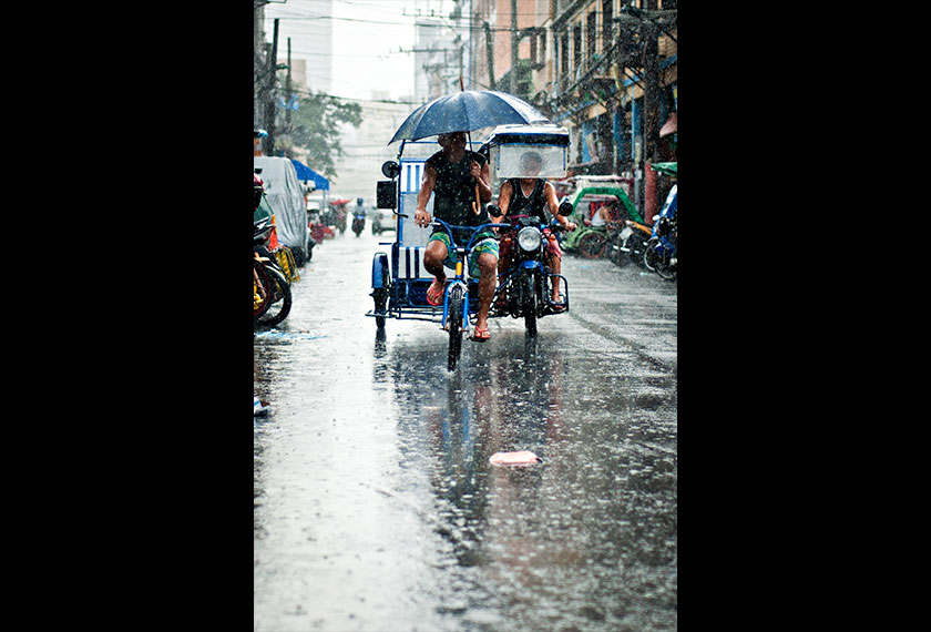 A tricycle driver and pedicab seen driving through the rain in Quiapo, Manila. - Photo by Karim Raslan
