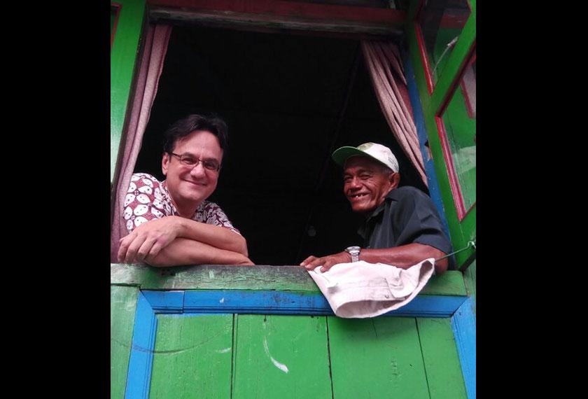 Pak Teguh looking out the window of his home alongside Karim. - Photo by Karim Raslan