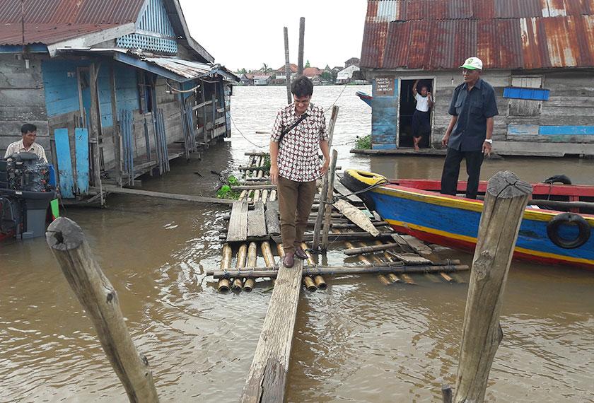 Karim precariously crosses the makeshift bridge connecting the dock to land. - Photo by Karim Raslan