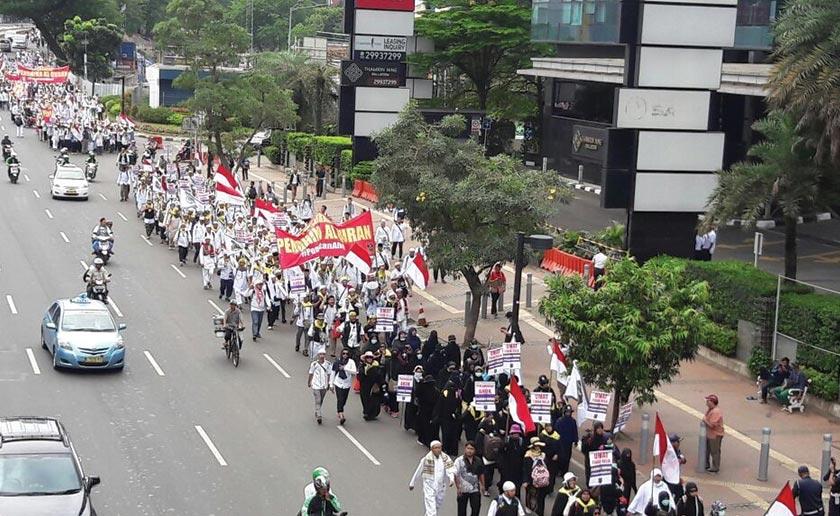 "People seen marching through the streets of Jakarta, demonstrating against then-Governor Basuki Tjahaja Purnama's (or ""Ahok"") ""blasphemous"" statements. - Karim Raslan Photo"
