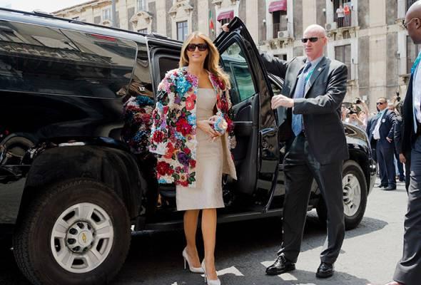 Melania tiba di majlis itu dengan memakai gaun berwarna krim, dibaluti jaket bercorak flora di bahagian luar berjenama Dolce & Gabbana.