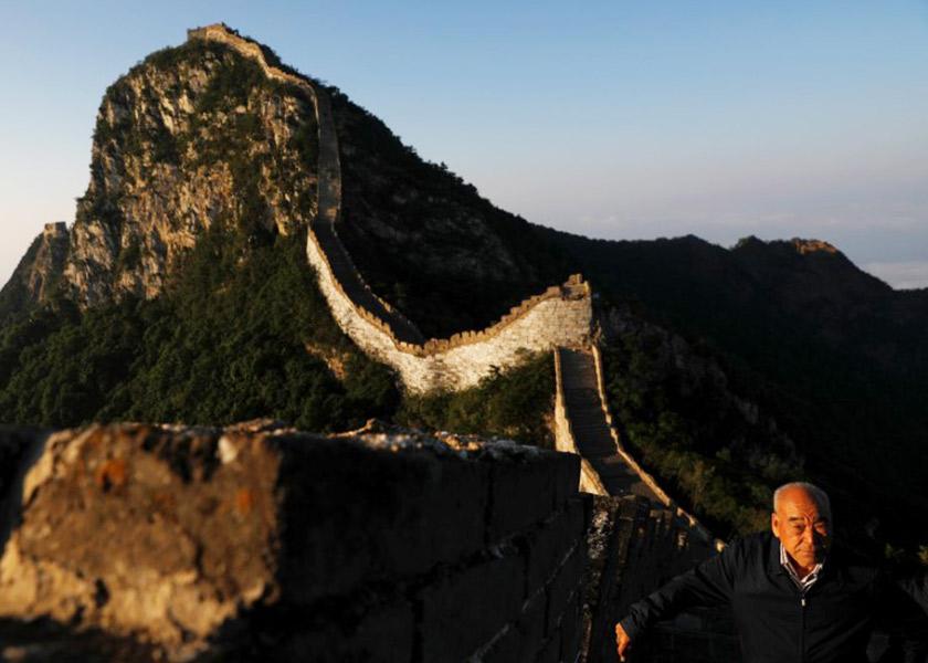 Cheng Yongmao, jurutera yang mengetuai pemulihan Jiankou, melihat matahari terbit dari belakang tembok, di daerah Hualrou, utara Beijing, China.