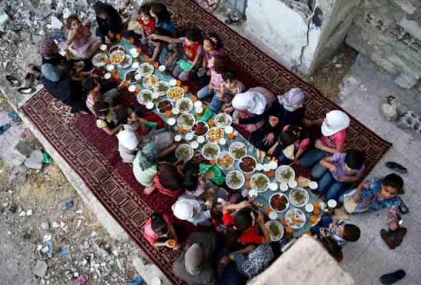 Hungry Syrians sat down together on the rubble-strewn streets to break fast with a free Ramadan meal.