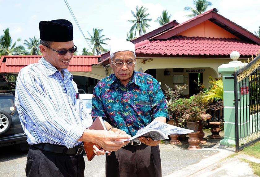 Hussin (kanan) berbual dengan jiran, Mohd Sabri Alias di hadapan rumahnya di Felda Lui Timur. - Bernama