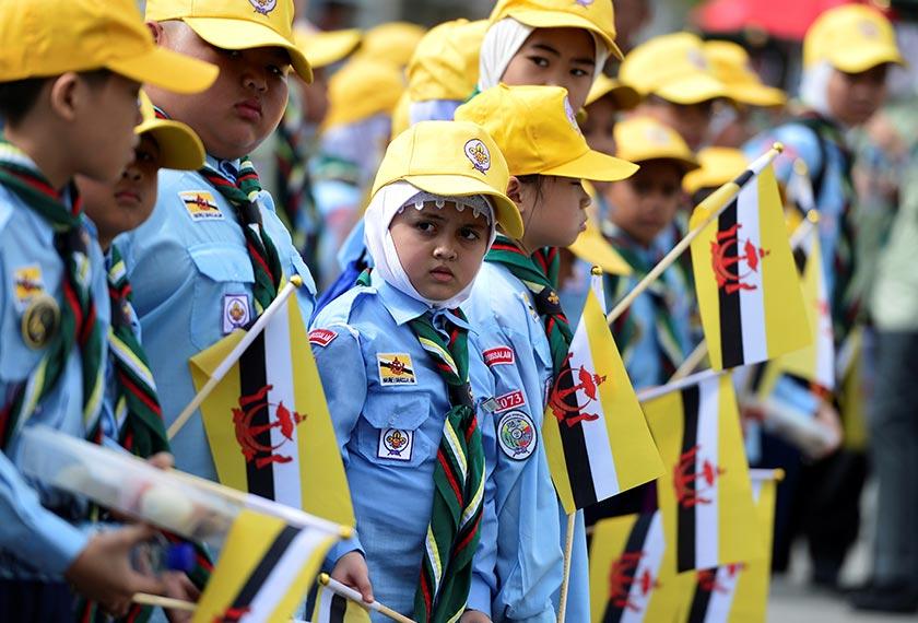 Aksi meriah kumpulan kanak-kanak dengan pakaian seragam yang turut meraikan upacara perarakan Sultan Brunei di jalanan. - Reuters