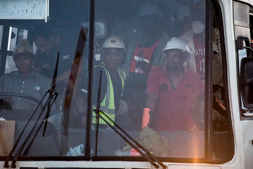 Pekerja lombong yang terperangkap, dikumpulkan dan di bawa menaiki bas. Foto: AP