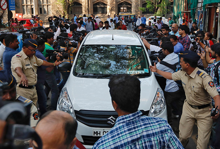 Police make way for a vehicle carrying three people suspected of steering fraudulent loans to companies linked to billionaire jeweller Nirav Modi, at a court in Mumbai, India, Feb 17, 2018. - REUTERS