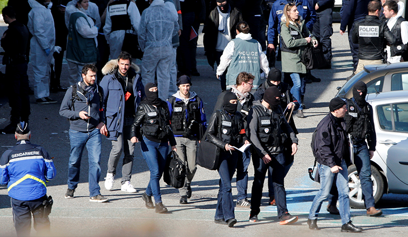 Police officers and investigators are seen in front of a supermarket after a hostage situation in Trebes, France, March 23, 2018. - REUTERS