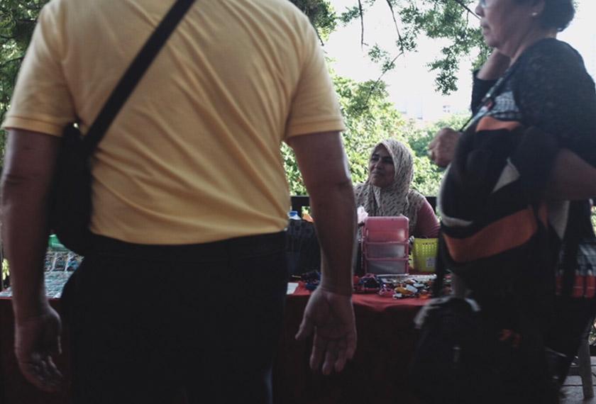 Kak Ani tak putus asa menegur setiap pelancong yang melintasi meja jualannya, mengharap ada yang singgah dan membeli. - Foto Astro AWANI/Israr Khalid
