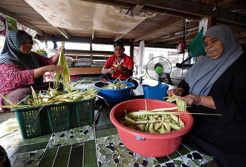 Zainab dibantu dua anaknya Mohd Azwan Ismail, 30, (tengah) dan Nor Aida, 41, (kiri) menyediakan ketupat palas yang ditempah oleh pelanggan ketika ditemui di Kampung Bukit Tunggal, pada Jumaat. - BERNAMA