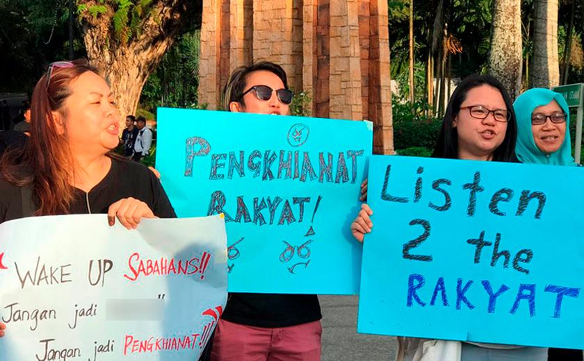 Kelihatan para penduduk Sabah berhimpun di luar pekarangan Istana Negeri membantah tindakan calon yang melompat parti.