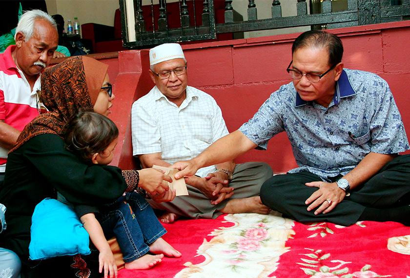 Wan Rosdy (kanan) menyampaikan sumbangan peribadi bagi meringankan beban kepada Noor Nadia (kiri) ketika menziarahi keluarga mangsa di Kampung Baru, Beserah, hari ini. - BERNAMA