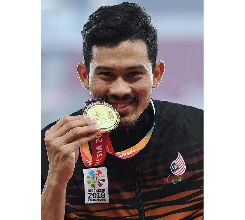 Atlet negara Abdul Latif Romly menunjukkan pingat emas yang dimenangi dalam acara akhir lompat jauh kategori lelaki T20 sempena Temasya Sukan Para Asia 2018 di Stadium Gelora Bung Karno. - Foto Bernama