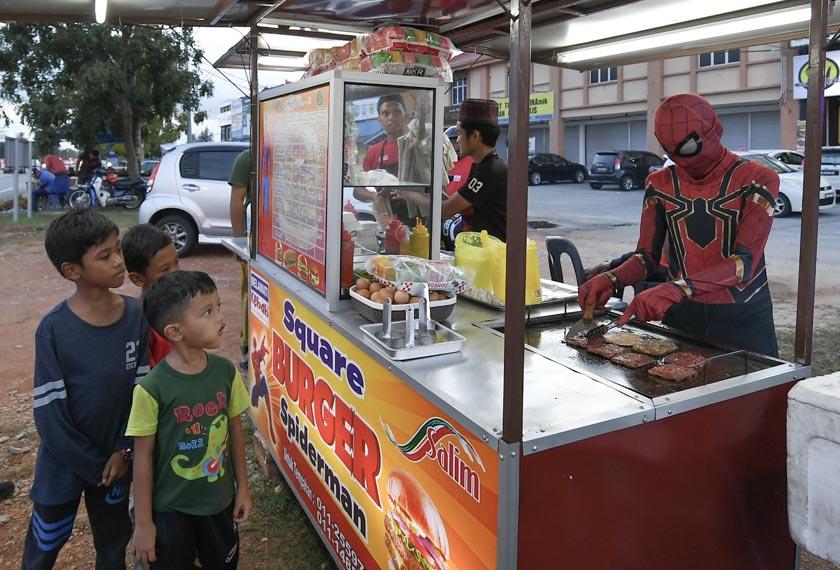 Fakhrul Fahmie Ishak, 18, (kanan) menggayakan kostum adiwira Spiderman turut membantu abangnya abangnya Ahmad Ridhuan, 22, (kiri) menyediakan pesanan burger di Kampung Raja