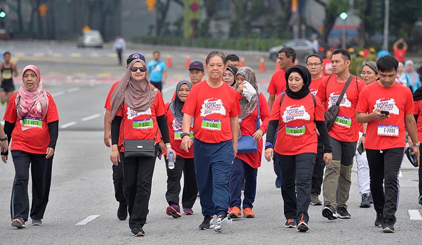 Mohamaddin Ketapi (tengah) meluangkan masa menyertai larian sejauh satu kilometer sempena Larian Ulat Buku U-Pustaka 2019 di Dataran Merdeka pada Ahad. - BERNAMA
