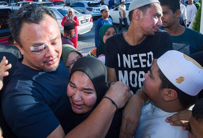 Suami arwah, Ahmad Shah menenangkan salah seorang anaknya di rumahnya di Kampung Paloh hari ini. --fotoBERNAMA