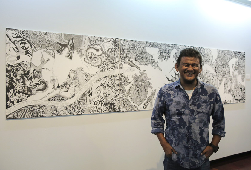 Ebby Yus disamping lukisannya yang dipamerkan di Galeri Shah Alam. - Foto: Astro AWANI/Shahir Omar
