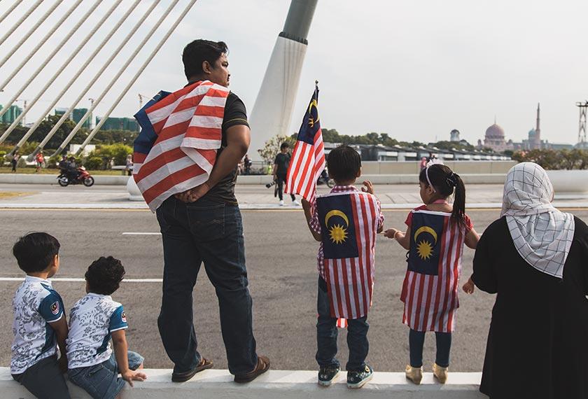 Seorang lelaki bersama dua anaknya memakai pakaian Jalur Gemilang menunggu bermulanya perarakan sempena sambutan Hari Merdeka di Putrajaya. Pasukan Ceritalah