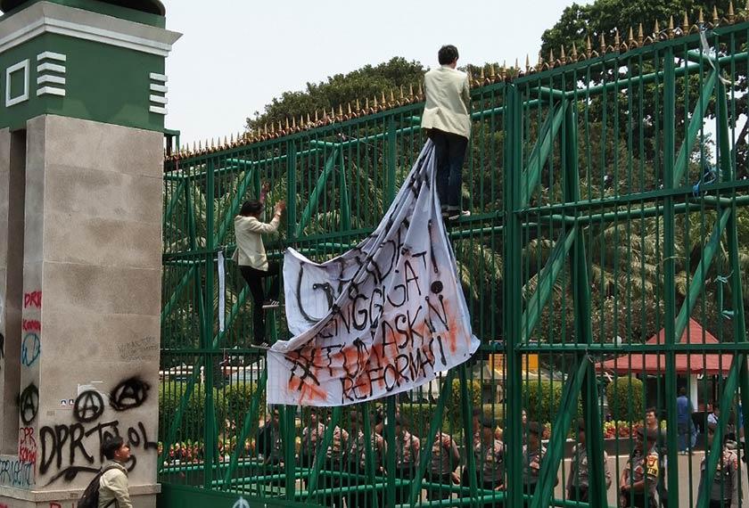 Penunjuk perasaan mengikat sepanduk pada pintu masuk utama bangunan DPR. Pasukan Ceritalah