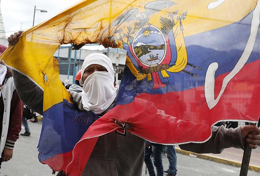 Seorang penunjuk perasaan memegang bendera negara yang telah koyak ketika mengadakan demonstrasi menentang Presiden Lenin Moreno dan dasar-dasar ekonominya di Quito, Ecuador, 8 Okt, 2019. (Foto AP)