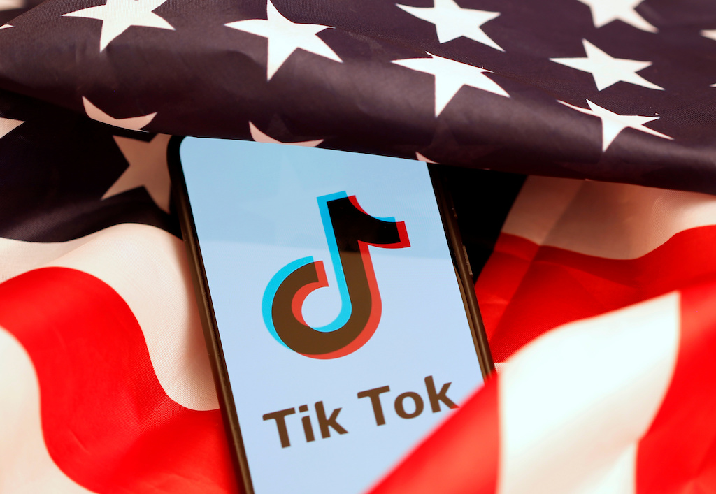 Tik Tok logo is displayed on the smartphone while standing on the U.S. flag in this illustration picture taken, November 8, 2019. REUTERS/Dado Ruvic