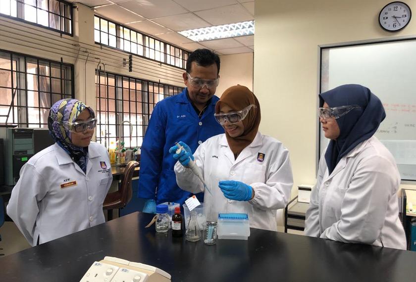 Dr. Azri memantau pelajarnya membuat penyediaan di dalam makmal.