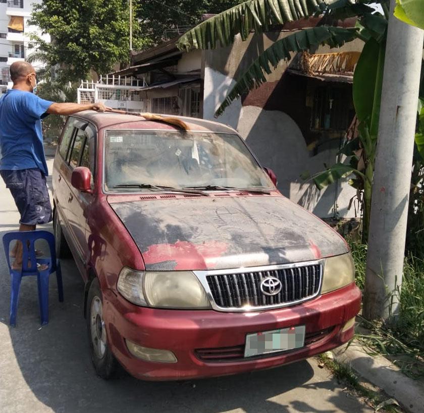 Adriano membersihkan debu volkanik di kenderaannya. Foto Ceritalah
