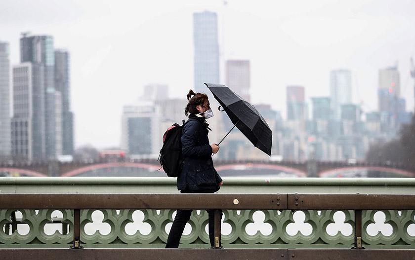 Seorang lelaki yang memakai penutup muka dan hidup berjalan di Jambatan Westminster di London, Britain, pada 5 Mac, 2020. - REUTERS