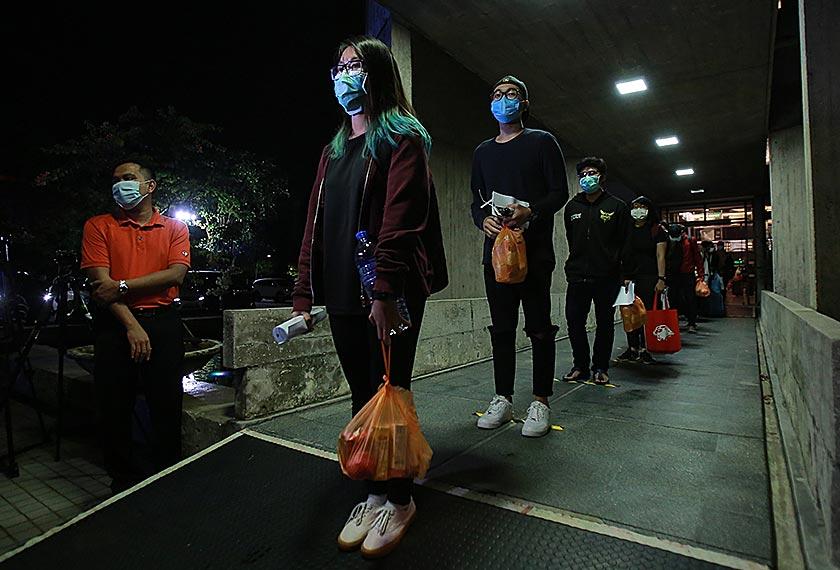 Penuntut UM dilihat memakai topeng muka dan mengamalkan penjarakan sosial sewaktu beratur untuk menaiki bas yang disediakan. - gambar Universiti Malaya
