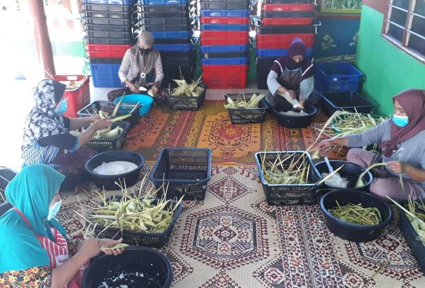 Che Non dibantu beberapa pekerja menyiapkan tempahan ketupat palas yang diterima. - Foto Astro AWANI