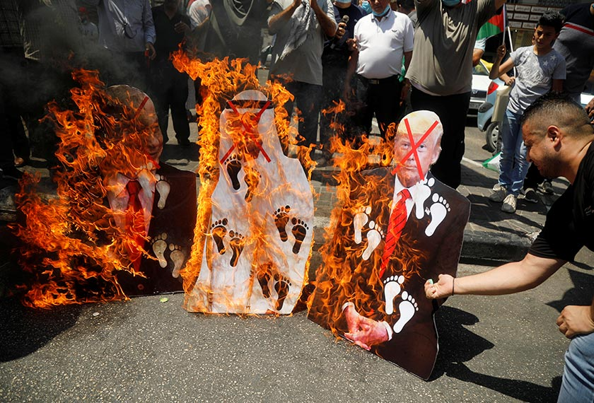 Palestinians burn cutouts depicting U.S. President Donald Trump and Abu Dhabi Crown Prince Mohammed bin Zayed al-Nahyan and Israeli Prime Minister Benjamin Netanyahu during a protest against the United Arab Emirates' deal with Israel to normalise relations, in Nablus in the Israeli-occupied West Bank August 14, 2020. REUTERS/Raneen Sawafta
