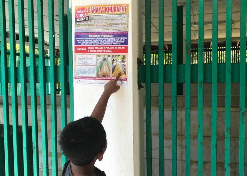Poster Bahaya Khurafat dapat dilihat di kawasan perkuburan di Pulau Besar