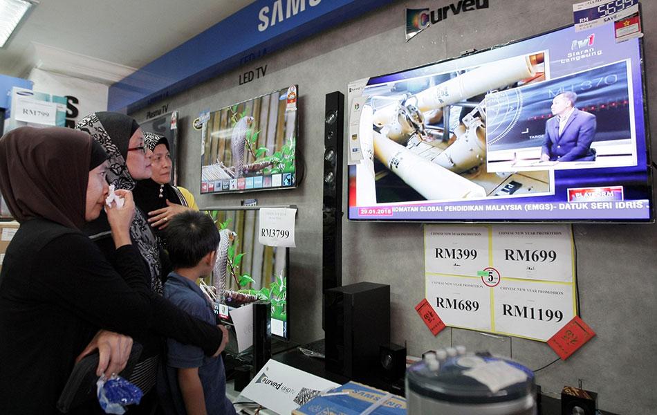 Orang ramai menanti untuk mendengar pengumuman yang disampaikan oleh Jabatan Penerbangan Awam (DCA) pada sidang media khas mengenai kehilangan pesawat Malaysia Airlines (MAS) MH370 yang disiarkan secara langsung di televisyen di sebuah kedai elektrik pada Khamis. Sidang media tersebut dijadual berlangsung pukul 3.30 petang tadi, namun ia dibatalkan atas sebab-sebab tertentu. - fotoBERNAMA