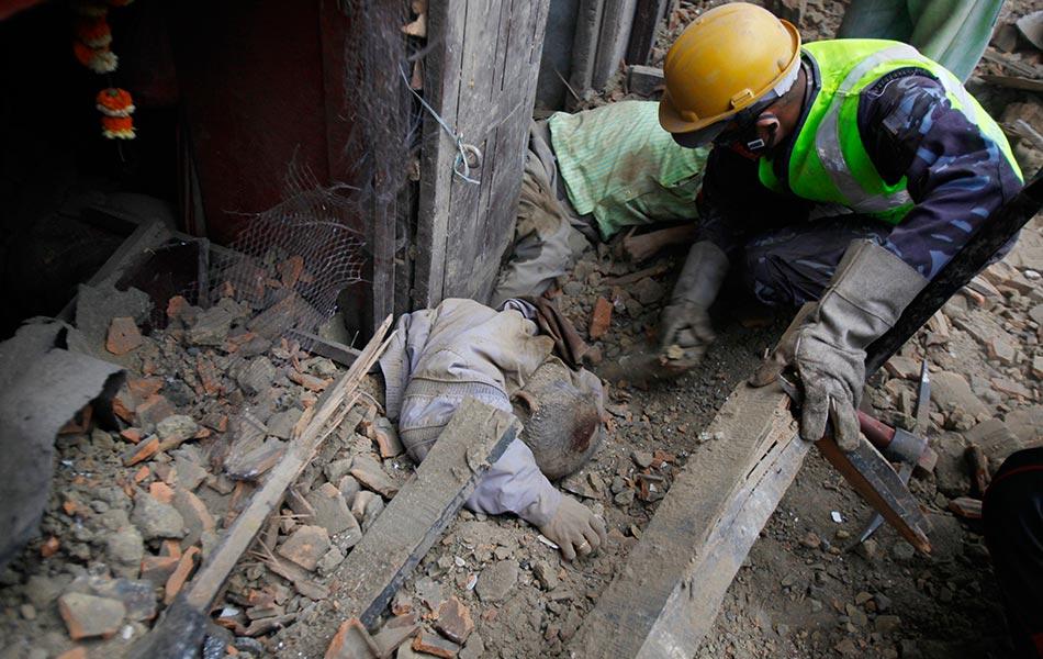 Seorang anggota penyelamat Nepal sedang mengalihkan bongkahan batu sejurus menemui satu mayat di bawah kesan runtuhan selepas kejadian gempa bumi pada Sabtu.-(AP Photo/ Niranjan Shrestha)