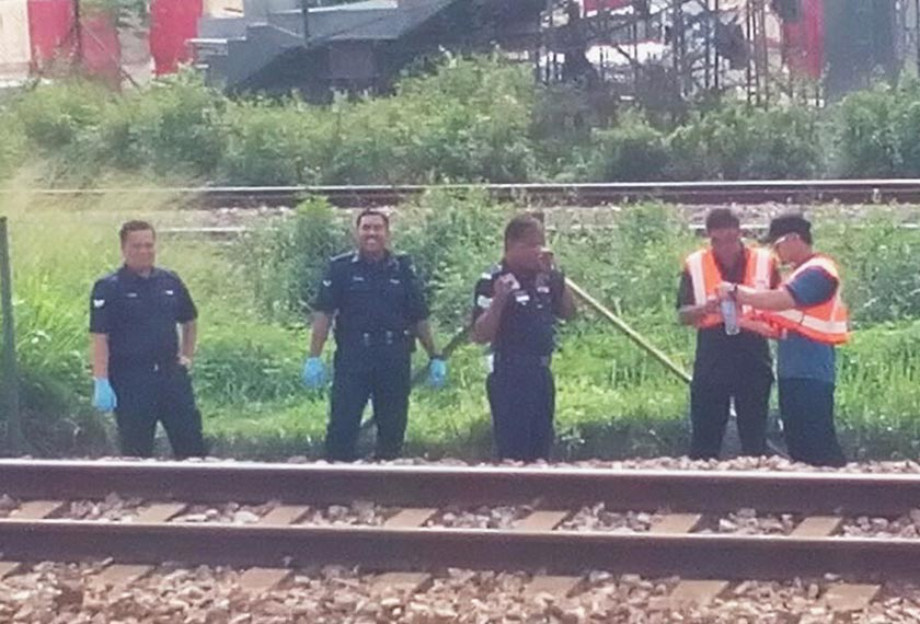 Police officers checking the area where Lee was hit by a KLIA Ekspres train this morning. - Astro AWANI