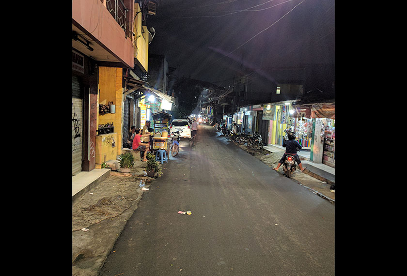 The narrow street in Lontar Atas is alive with cars and people even at night. - Karim Raslan Photo