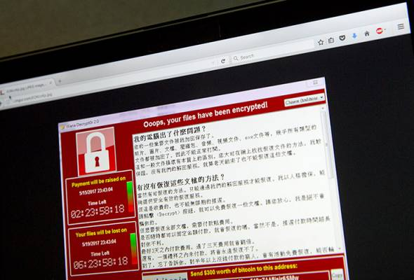 FILE PHOTO: A screenshot of the warning screen from a purported ransomware attack, as captured by a computer user in Taiwan, is seen on laptop in Beijing. - AP | Astro Awani