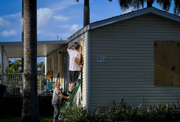 Yana and Jeremy Cauble board up their mobile home in preparation for Hurricane Irma in Homestead, Florida, U.S., September 7, 2017. REUTERS/Bryan Woolston | Astro Awani