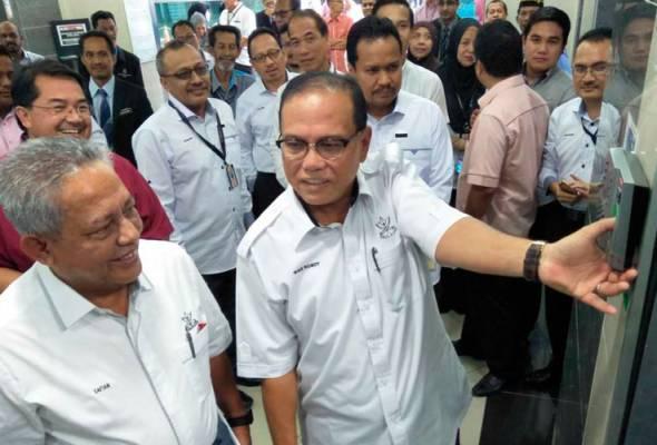 Wan Rosdy (kanan) mengetik perakam waktu ketika hadir memulakan tugas pada hari pertama di pejabatnya di Wisma Sri Pahang di sini, hari ini. | Astro Awani