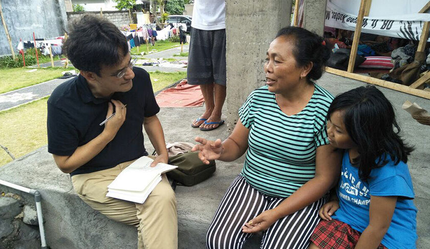 Karim speaks to 53-year-old Nyoman Gerti and granddaughter Gita after Gunung Merapi's eruption in November 2017. Ceritalah Photo